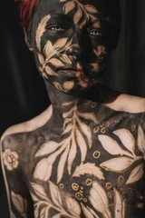 Portrait of a woman in black and gold body paint