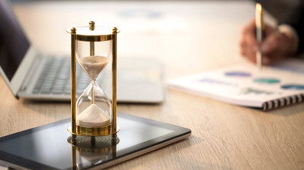 Time is running in hourglass, female manager checking graphs at office desk