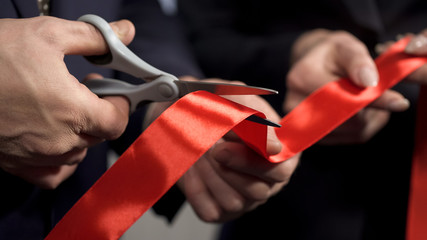 Business people hands cutting red ribbon close-up, new project, opening ceremony