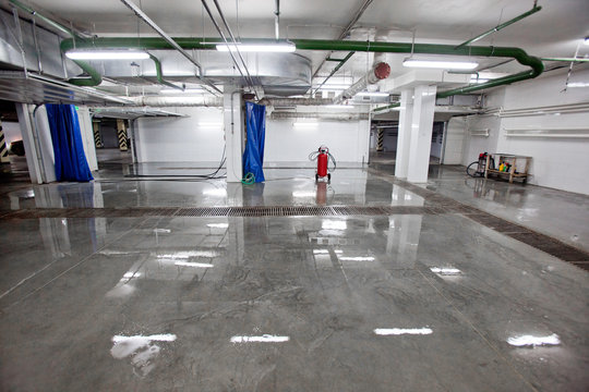 Inside shot of car washing area with glowing lamps reflecting light in wet floor.