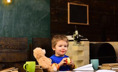 Happy childhood concept. Smiling kid eating juicy fruit. Kid holding bitten apple
