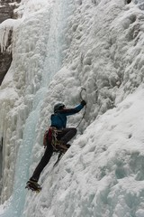 Male rock climber climbing ice mountain
