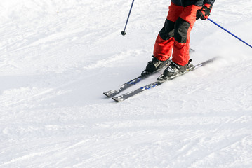 Downhill ski snow skier detail gear red trousers close-up
