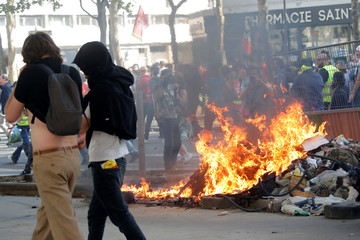 Protesters walk past burning debris after clashes during a demonstration against the French government's reform plans in Paris