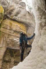 Male climber standing near rocky mountain