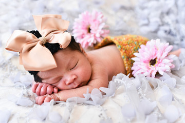 asian little baby newborn sleeping on a lace with flower pattern. newborn photo concept