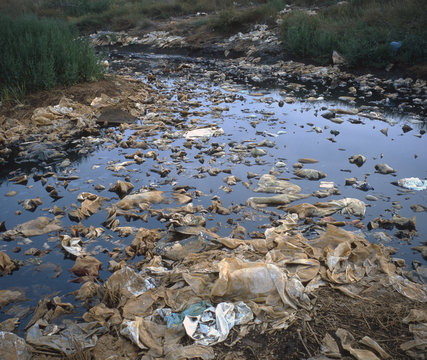 Plastic bags floating in leachate at base of hazardous landfill site.