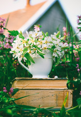 ceramic cup with white flowers on a pile of old books in a clearing with flowering herbs against the backdrop of a village house on a spring or summer sunny morning