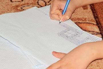 мальчик рисует кирпичный дом на листе бумаги
