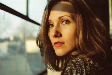 Close-up portrait of pretty young woman, looking at window, serious expression, refined, relaxed, chiselled thin face, fair hair, mild sunset light