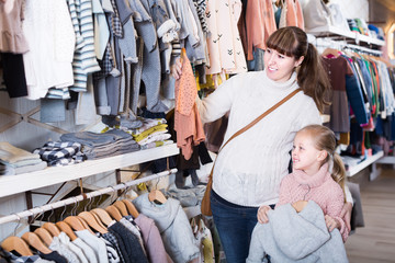 Mother and girl child choosing clothes for baby