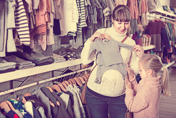 Pregnant mother and daughter choosing romper suit for baby in children's clothes shop