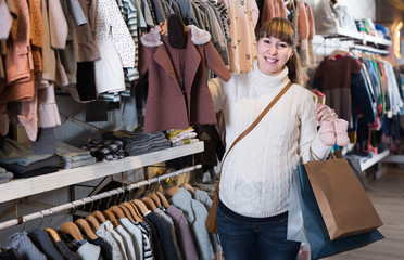 Pregnant woman showing her purchases in children's clothes shop