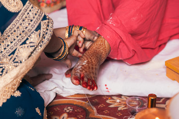 Indian bride in a Feet Coloring Ceremony during a Hindu wedding ritual.