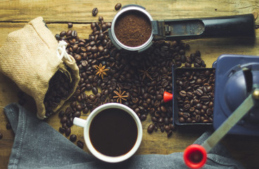 black coffee cup on old wood with coffee beans and old grinder