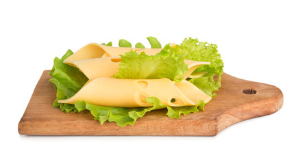 Cheese slices on green salad leaves background
