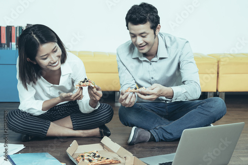Happy Asian office workers or students or couple sitting together on floor,  eating pizza and