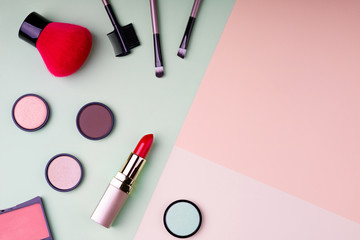Makeup products and decorative cosmetics on color background flat lay. Fashion and beauty blogging concept. Top view. Copy space