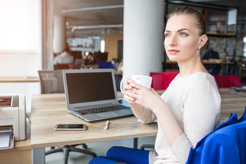 Beautiful woman is sitting in chair and holding a cup of tea. She took a pause after some hard-working time. She is relaxing and keeping her strenght to the next thing she needs to do.