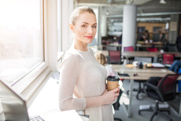 Beautiful girl is posing on camera. She stands near big and bright window and looking to the camera. Also she is holding a cup of coffee in her hands.