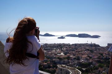 femme photographiant Marseille et les iles du frioul depuis Notre-dame-de-la-garde