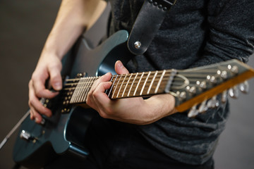 Male hands playing electric guitar