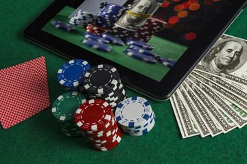Poker chips with a bunch of dollars near a black tablet