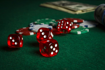 Dice on the poker table against the background of poker chips and dollars