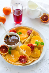 French pancakes. Crepe Suzette with caramel, oranges, blueberries, almonds and hazelnuts on white table cloth