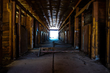 Empty horse stalls within an abandoned dilapidated barn with clean line shining through the open barn doors at the end of the room