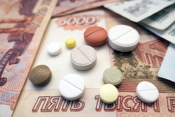 Different types of tablets located on Russian rubles close-ups
