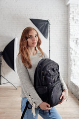 Young female photographer with backpack in modern photo studio