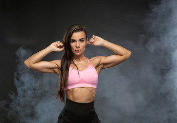 Image of fitness woman in sports clothing in the smoke. Young female model with muscular body. Horizontal studio shot with copy space on black background.