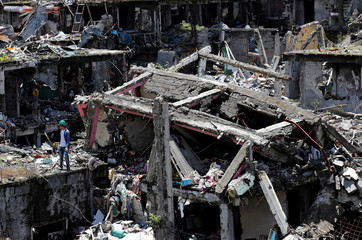 Residents walk through the ruins of their houses, after they were allowed to return to their homes for the first time since the battle between government troops and Islamic State militants began on May 2017, at the Islamic city of Marawi