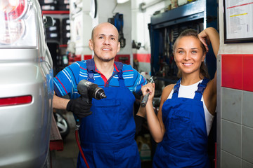 two mechanics in car fixing workshop.