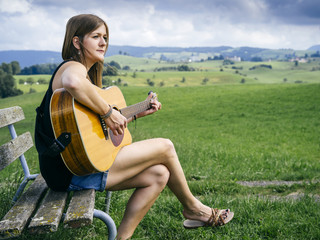 Woman playing guitar on a park bench