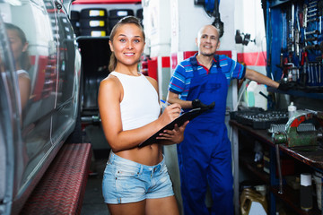 Woman standing and writing down data at car service