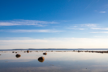 Stones and sky reflection in white sea low tide