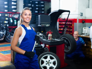 female technician standing with wheel balancing machinery at auto workshop