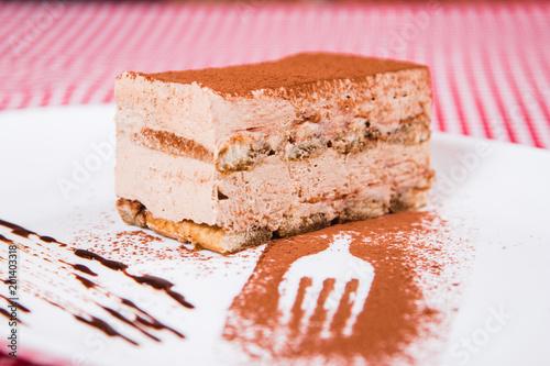 Delicious world famous Tiramisu cake on a white plate with ... on