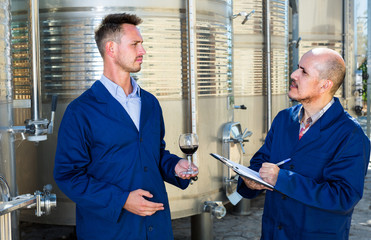 two experts men examining wine