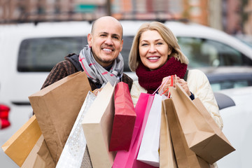 elderly couple carrying purchases and smiling outdoors