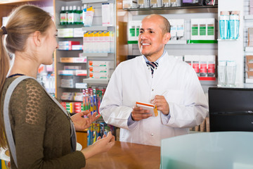 Pharmacist serving client in pharmacy .