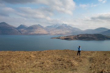 Woman taking a photo of the dramatic scenery of Ben More mountain across loch Na Kea, Isle of Mull, Scotland