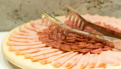 Ham and sausage on wooden plate