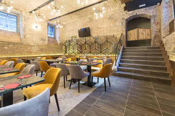 Interior of a modern hotel restaurant with brick wall