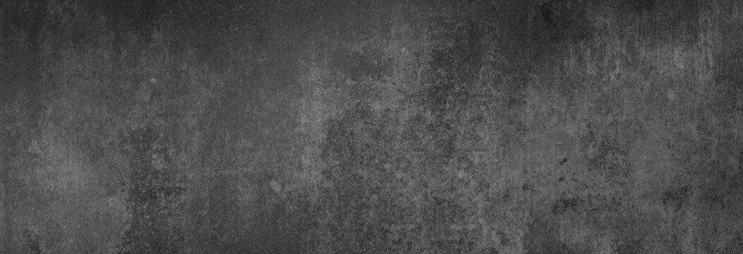 Textur einer fast schwarzen Betonwand in XXL-Größe als Hintergrund, auf die leichtes Licht fällt