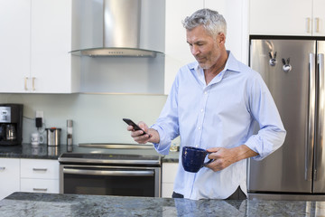 Gray-haired man texting while standing in kitchen with mug, Massachusetts, USA