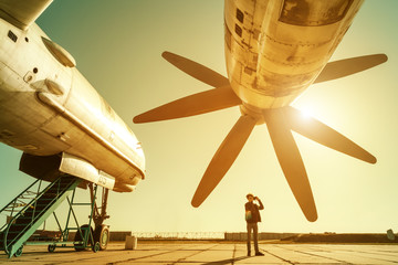 Boy stands under propeller of big plane and takes photo