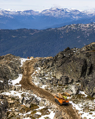 Small rock crawler machine carrying wood down rocky incline, Whistler, British Columbia, Canada